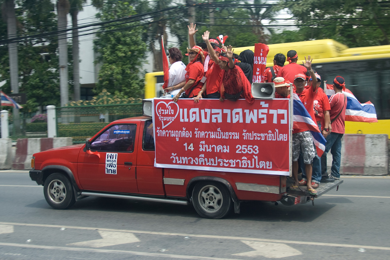 Red Shirt protesters on back of truck carrying Thai flags