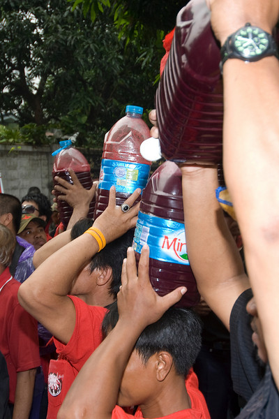 Men carrying water bottles on their head during Red Shirt Protest in Thailand