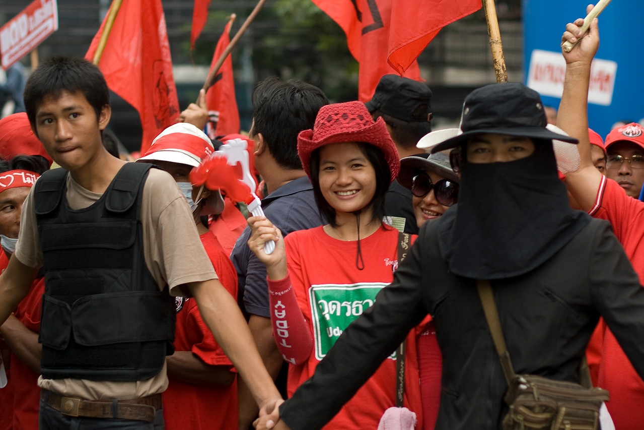 A woman smiles to the camera while in the middle of human barricade