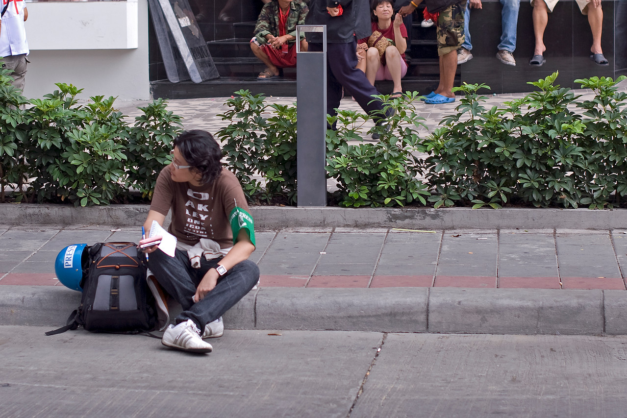 A member of the press sits down on a side walk - Thailand