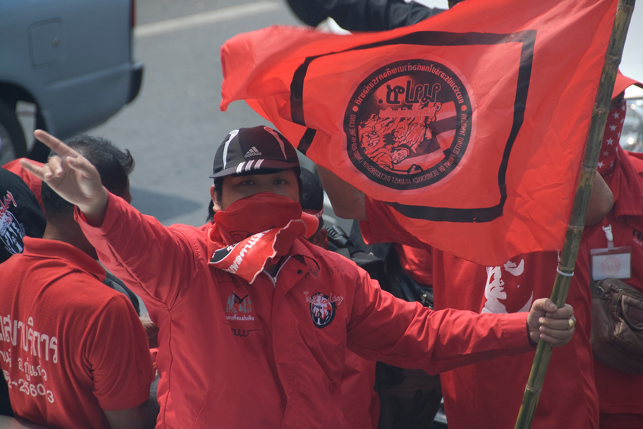 Man carrying flag during Red Shirt Protest in Thailand