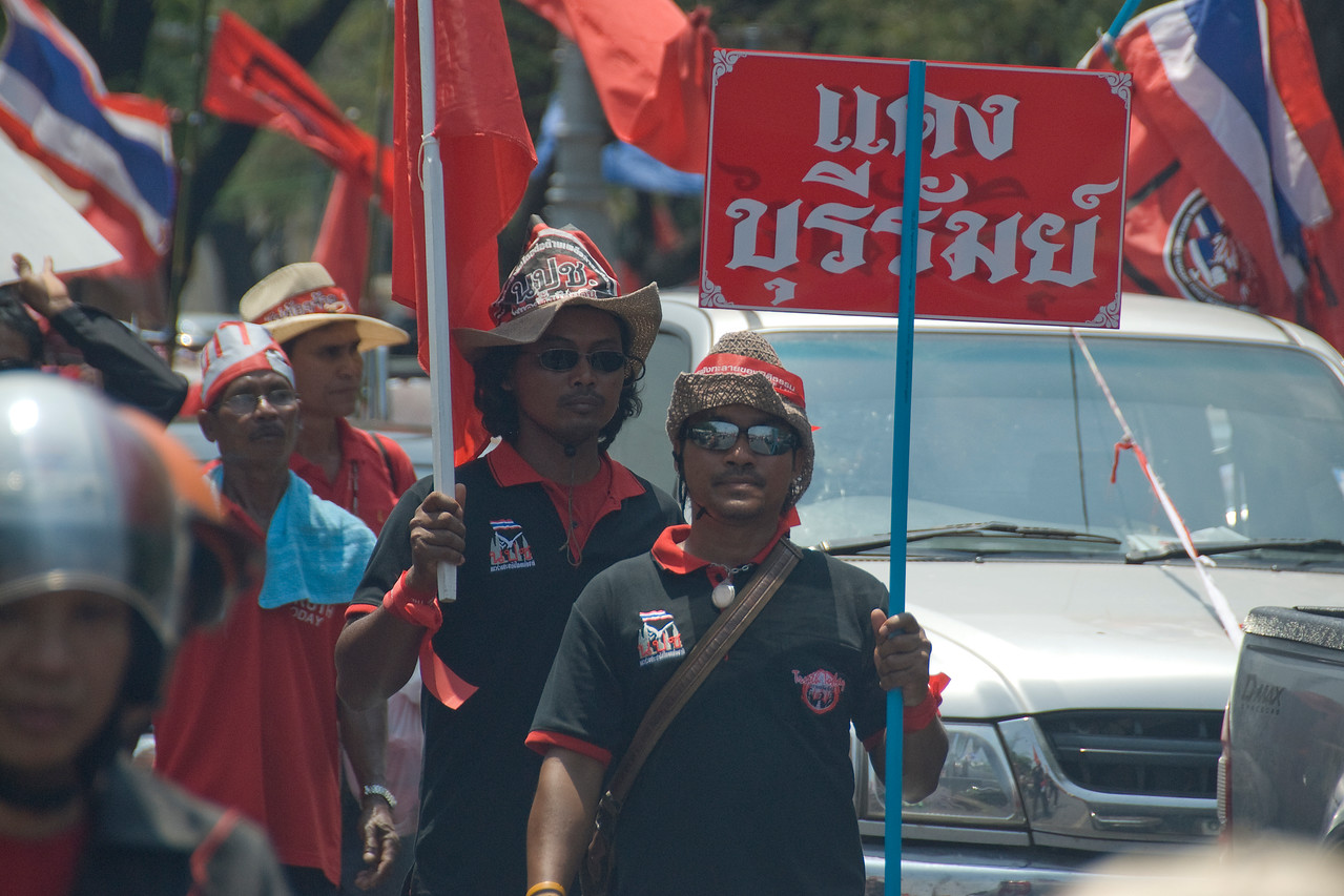 Men holding out signs while marching during Red Shirt Protest - Thailand