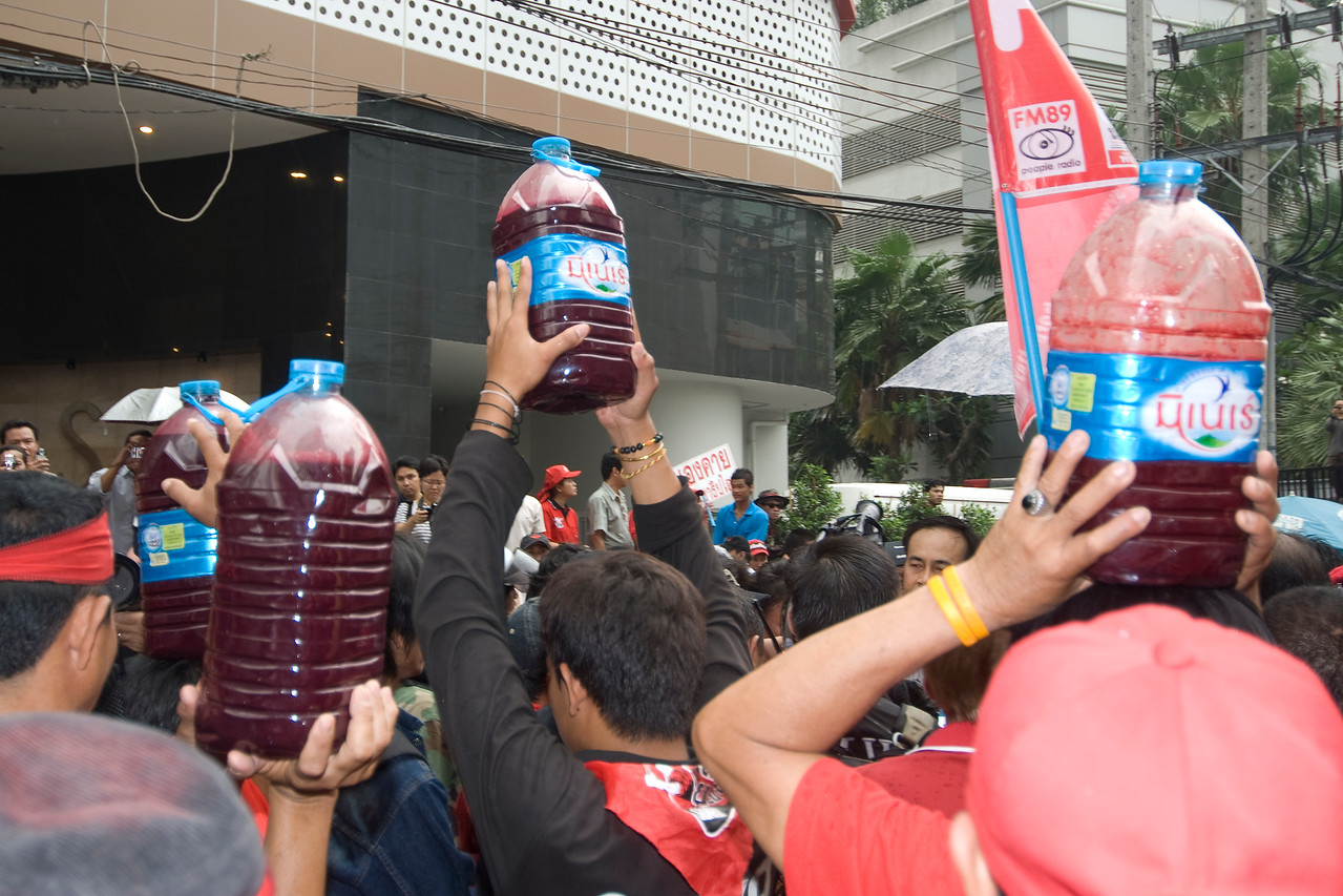Men carrying water bottles during Red Shirt Protest