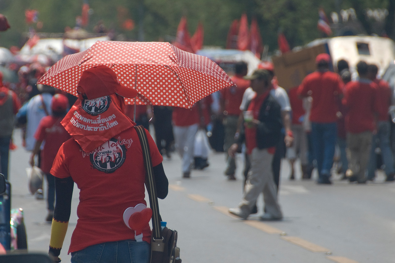 Woman carrying red umbrella during Red Shirt protest march