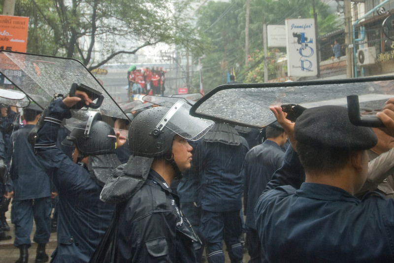 Riot police shielding themselves from the rain - Thailand