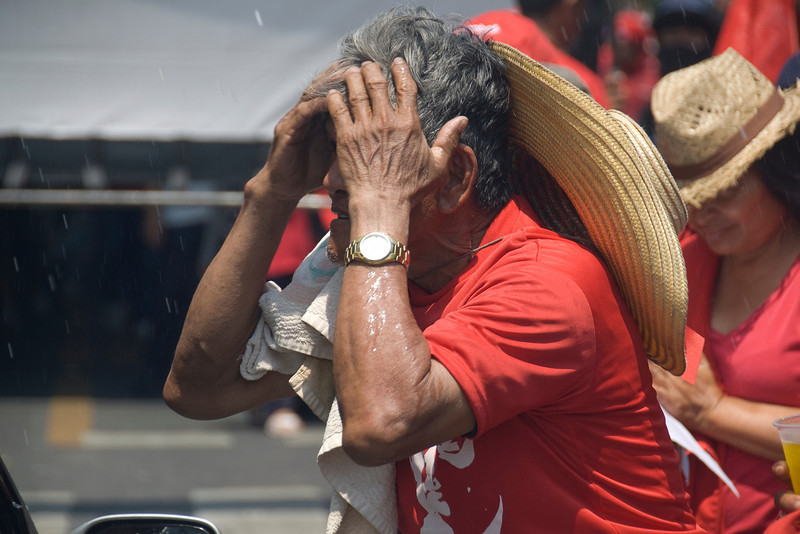 Man wiping his face from a drizzle of water during Red Shirt Protest in Thailand