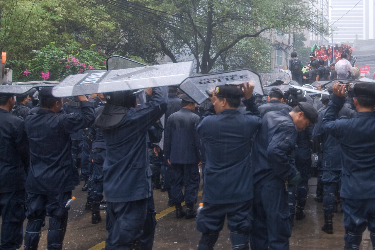 Riot police using their shield as cover from rain - Thailand