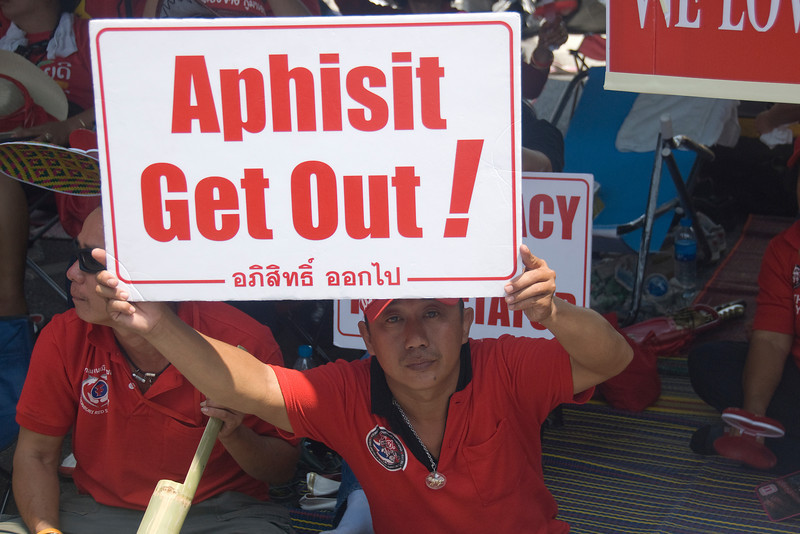Man in red shirt holding out protest sign - Thailand