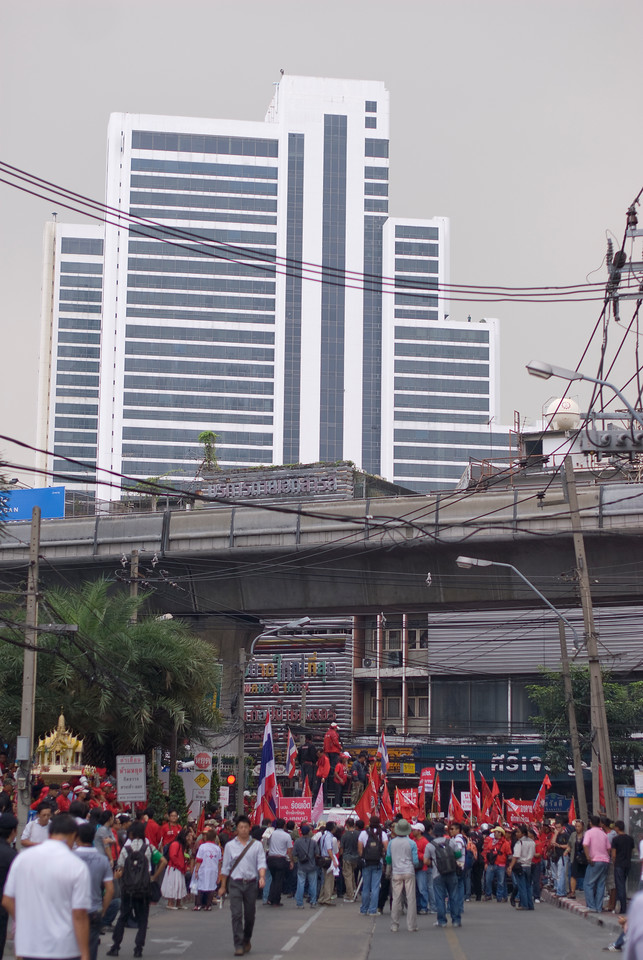 Shot of flyover and skyscraper above Red Shirt protesters
