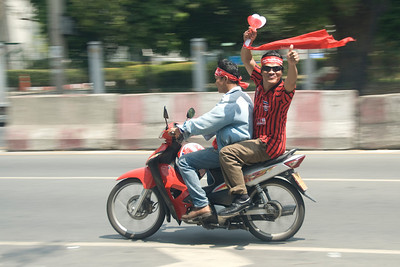 Man giving a thumbs up while riding motorcycle during Red Shirt Protest in Thailand
