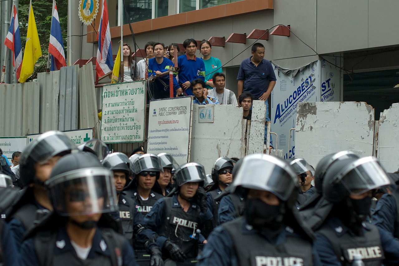 Onlookers and riot police during the Red Shirt Protest in Thailand