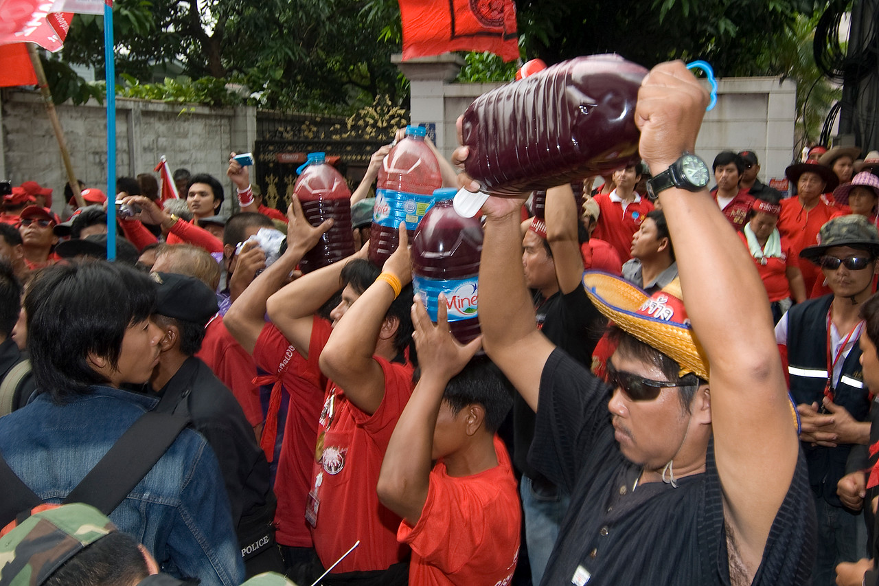 Men carrying jug with colored water during Red Shirt Protest