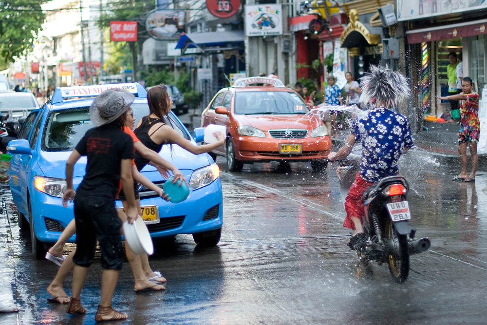 Throwing water at a motorcyclist during Songkran celebrations in Thailand