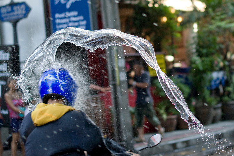 Water hits man wearing helmet while driving motorcycle at the Songkran Festival