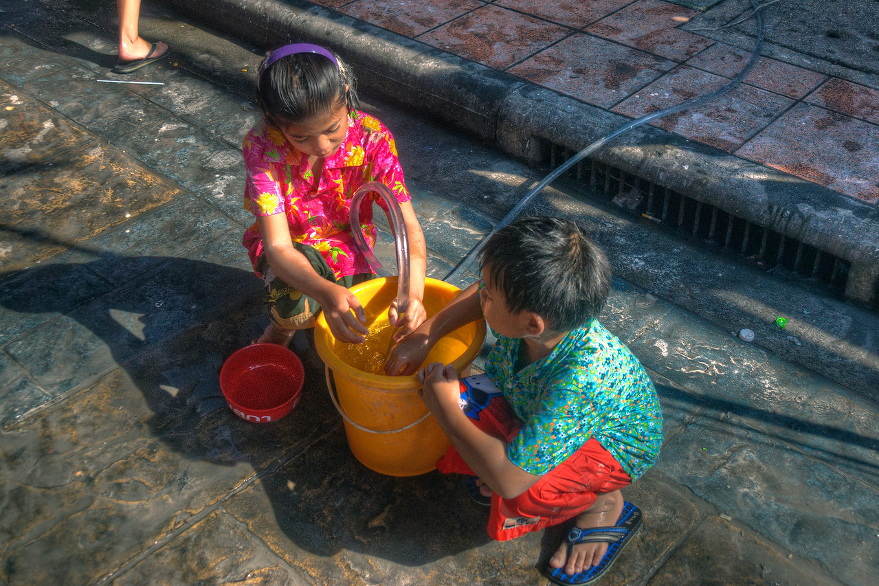 Kids catching water on a bucket in Thailand