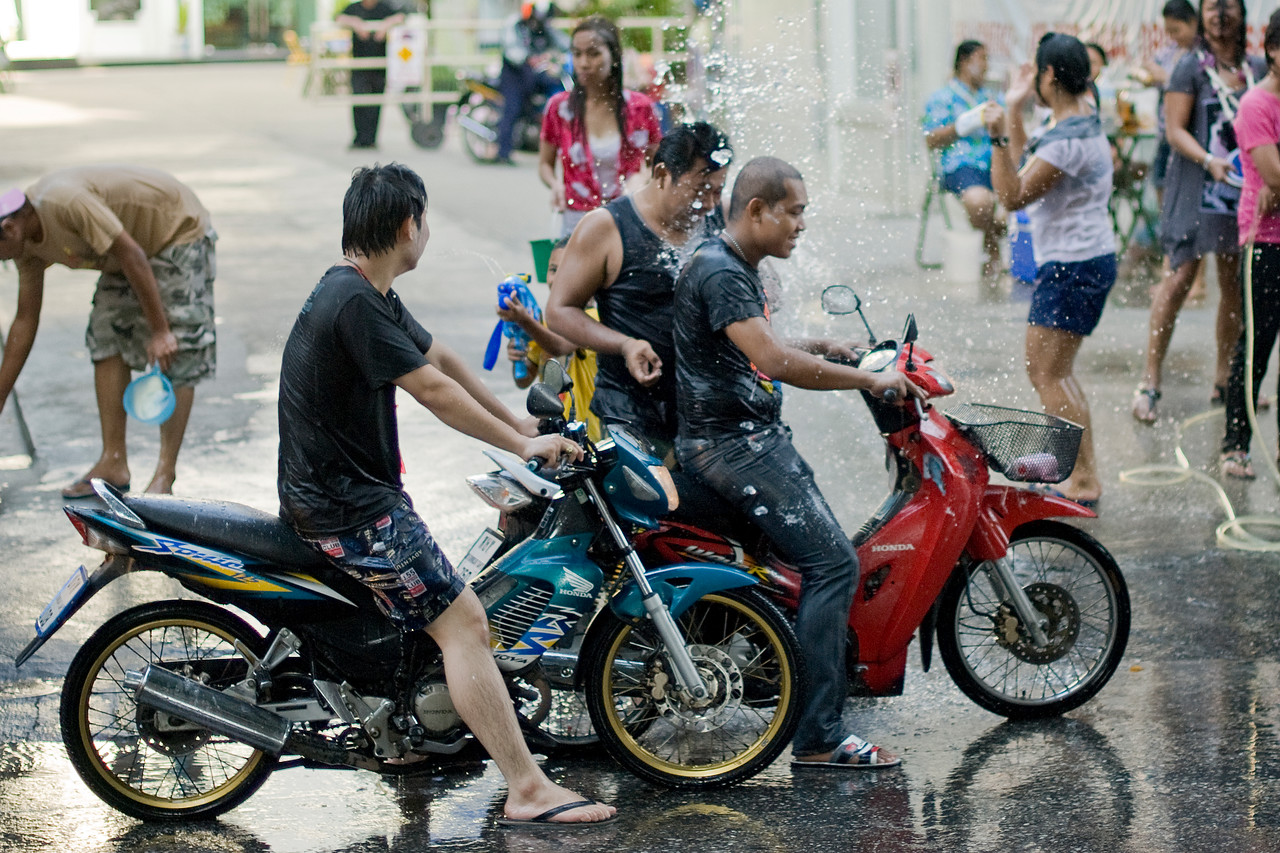 Men in motorcycle being sprayed on with water - Thailand