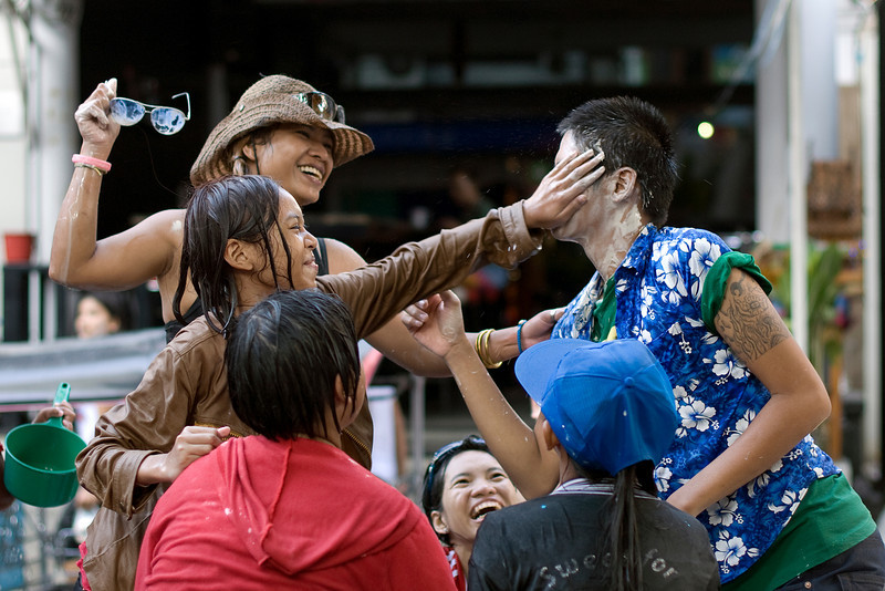 Women wiping off paint off a man's face at the 2010 Songkran Festival