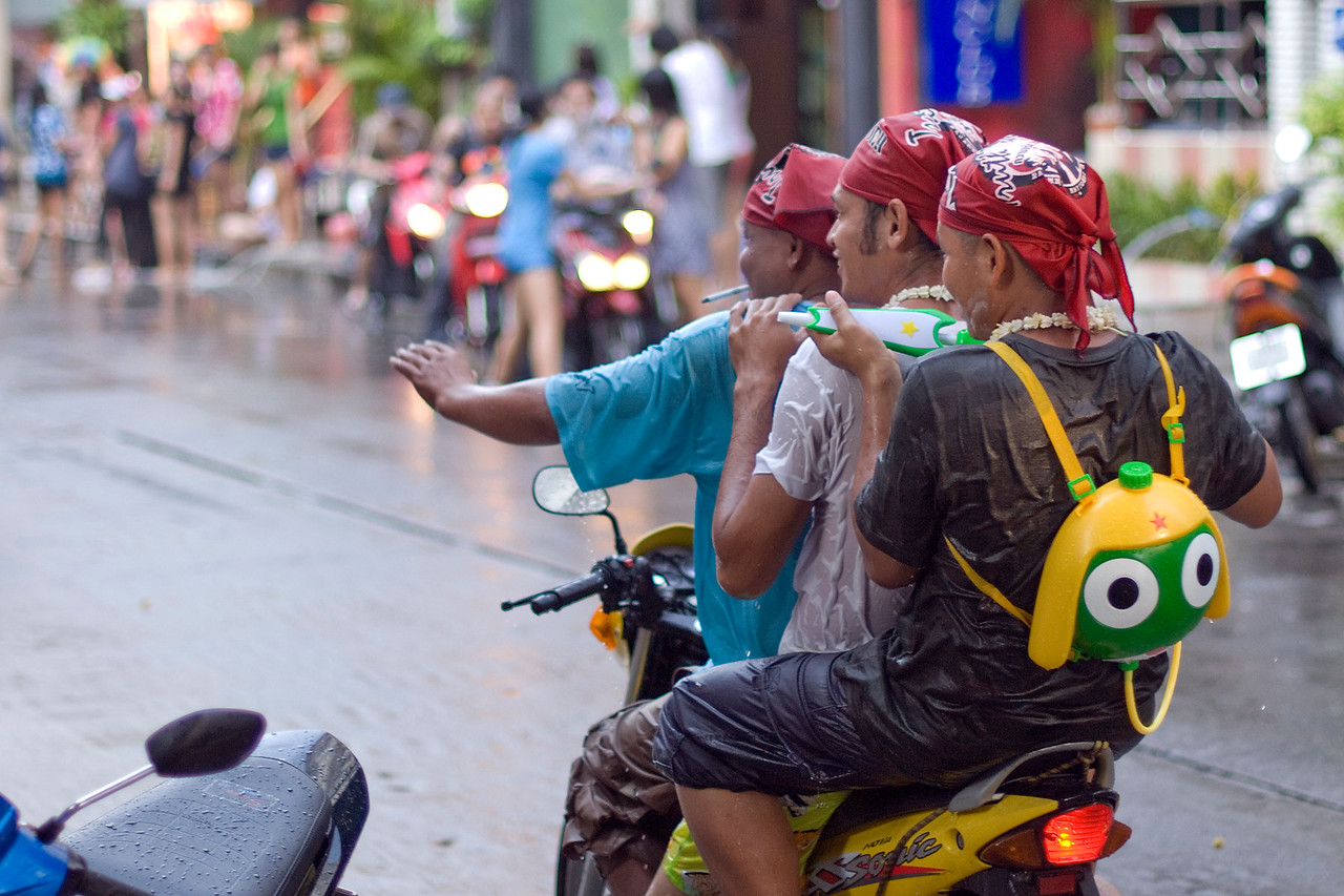 Motorcycle-riding men spraying on water to onlookers at the 2010 Songkran Festival