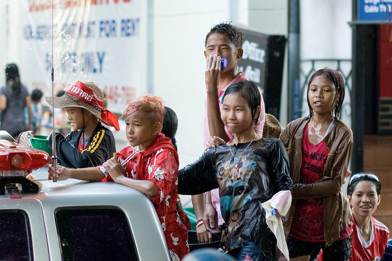 Closer shot of kids riding from back of truck during Thailand's Songkran Festival