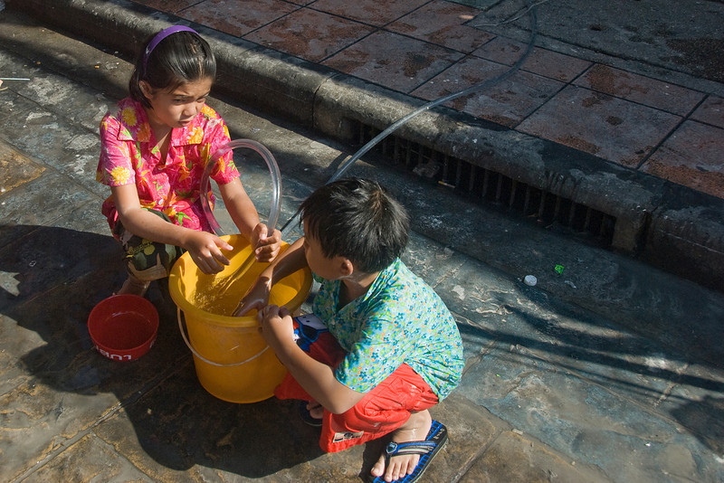 Kids catching water on a bucket - Thailand