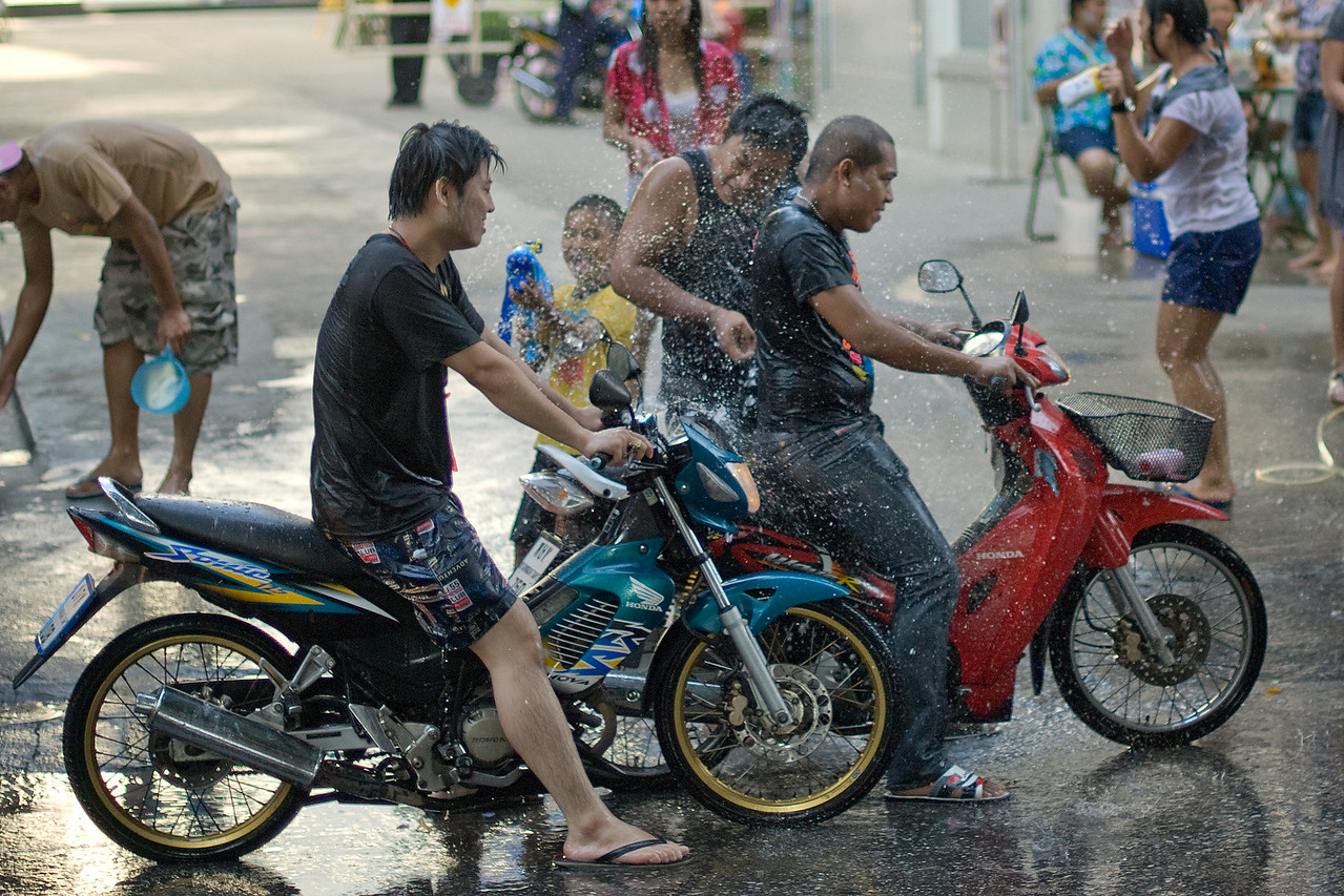 Men on motorcycles are splashed with water by onlookers at the 2010 Songkran Festival