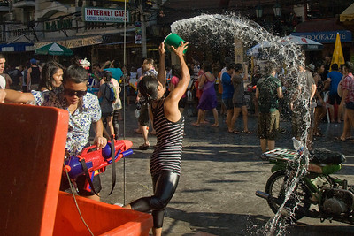 The crowd getting a shower of water from a local female in the Songkran Festival in Thailand