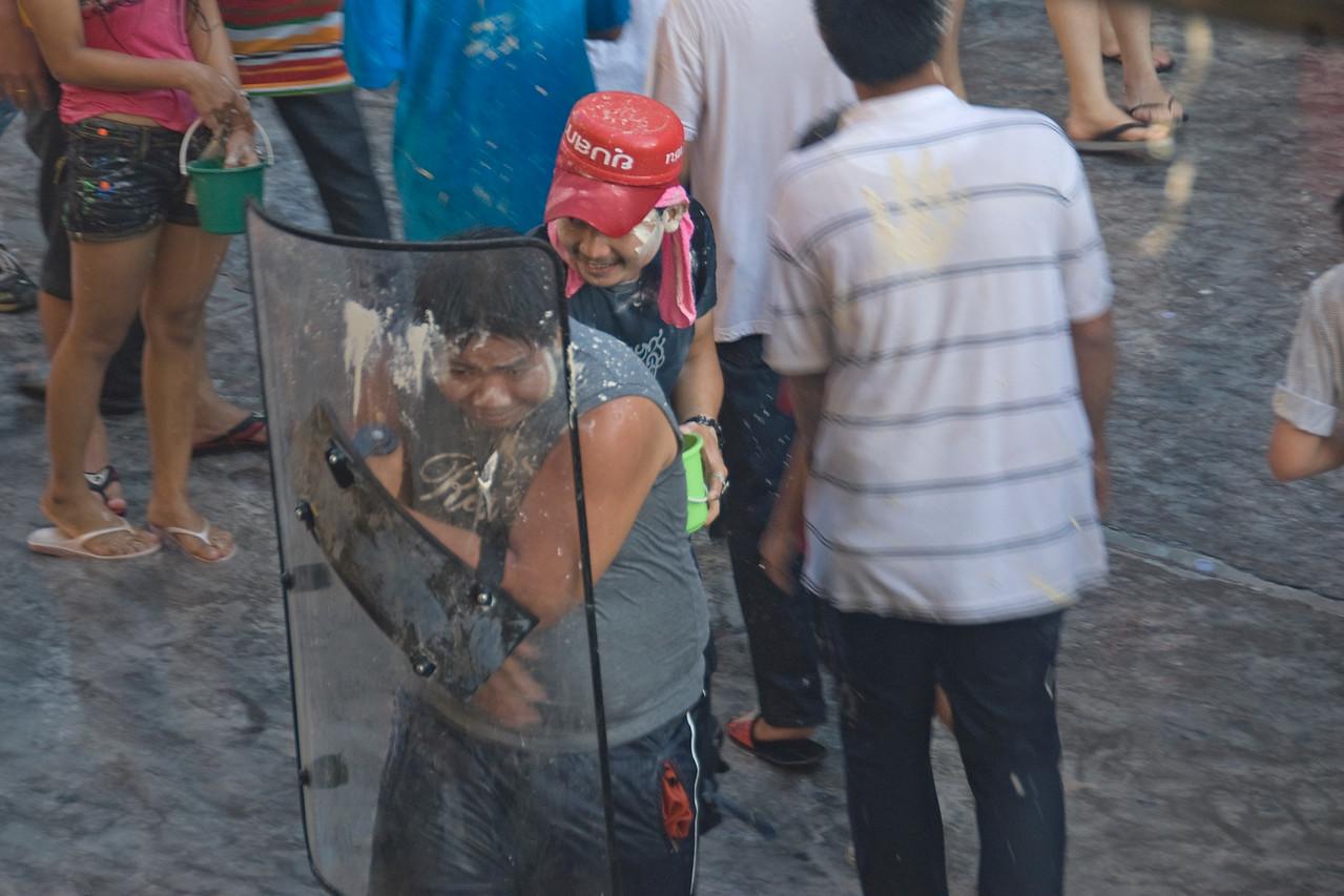 Man shielding himself from paintball shots in the 2010 Songkran Festival