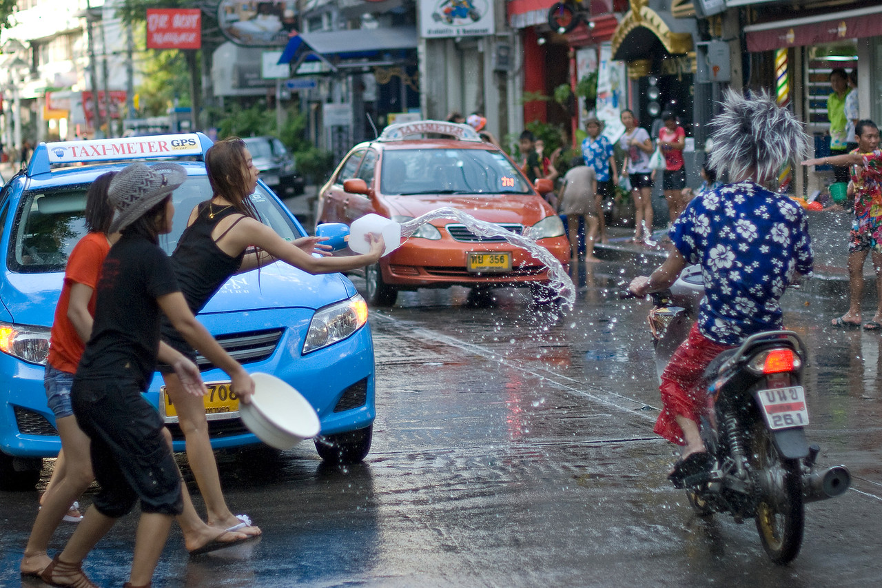 Woman tossing water onto a motorcycle-riding man - Songkran Festival, Thailand