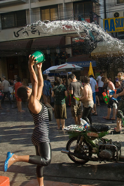 A woman hoists water onto the crowd at the 2010 Songkran Festival