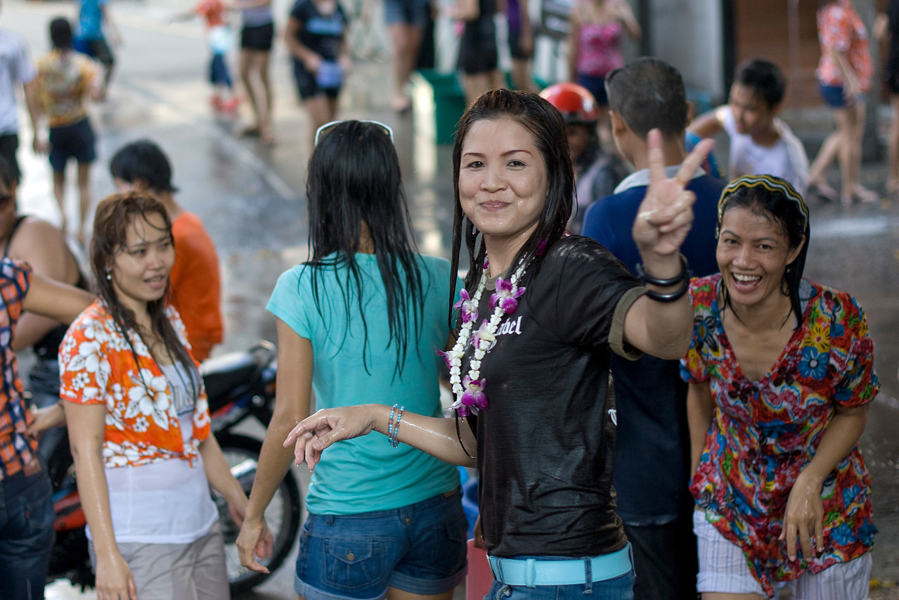 Woman holds out peace sign to the camera at the Songkran Festival celebration