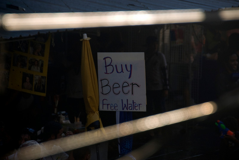 """""""Buy Beer, Free Water"""" sign at a stall in the 2010 Songkran Festival"""