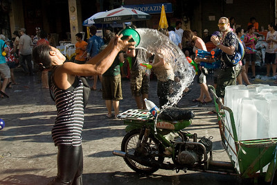 Woman throwing bucket of water onto the crowd at the 2010 Songkran Festival
