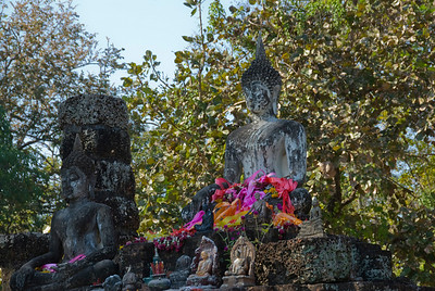 Flowers and offerings at Buddha statue in Wat Phra Phai Luang - Sukhothai, Thailand