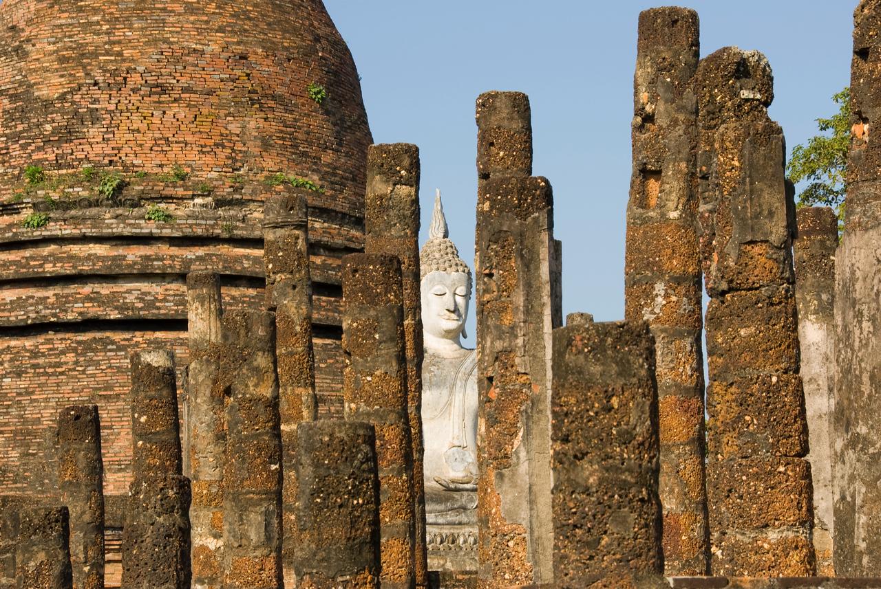Peeking at Buddha through posts in  Wat Mahathat - Sukhothai, Thailand