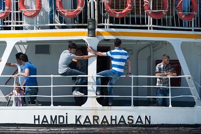 Men sitting on rail at boat - Istanbul, Turkey