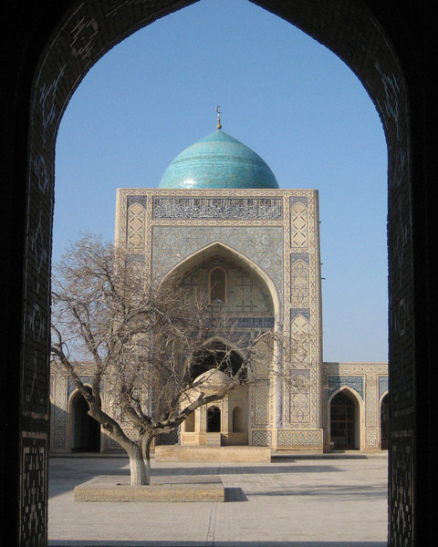 The entrance to the Kalyan Mosque courtyard with a solitary tree in the ancient city of Bukhara.