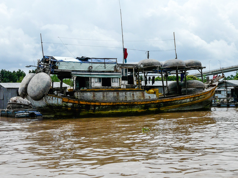 Rusted boat cruising the muddy Mekong River.