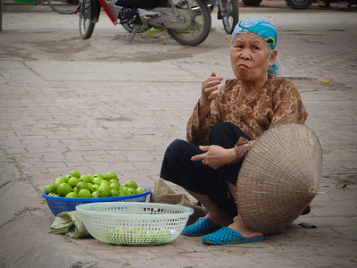 Hanoi guava is smaller and more sour than that found down south. From the look on her face this vendor appears to be eating her own product.