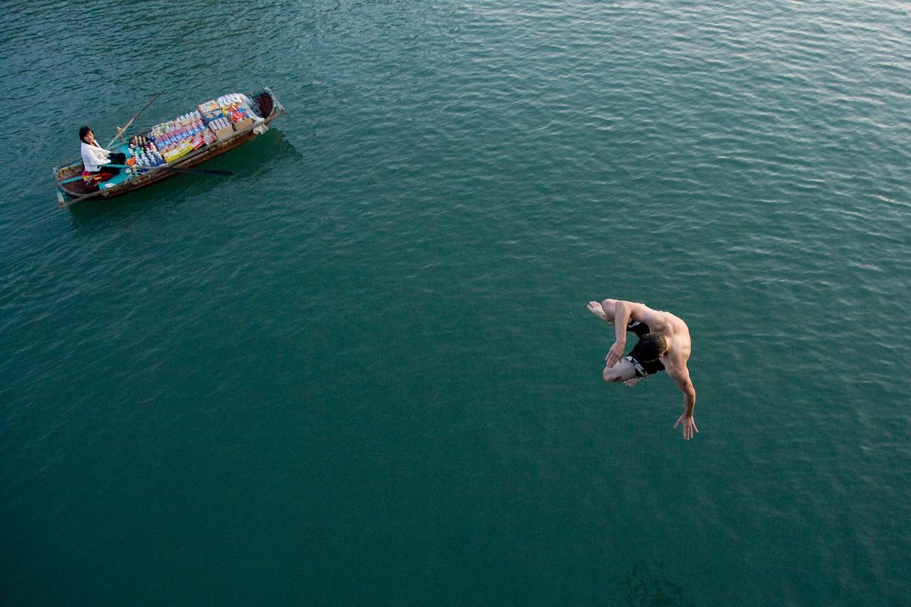 Man jumping off the boat in Ha Long Bay, Vietnam