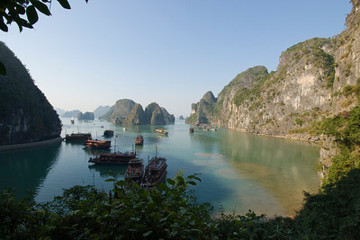Boats close to the islands and cliffs in Ha Long Bay, Vietnam