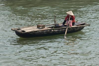 Woman sits on a row boat in Ha Long Bay, Vietnam