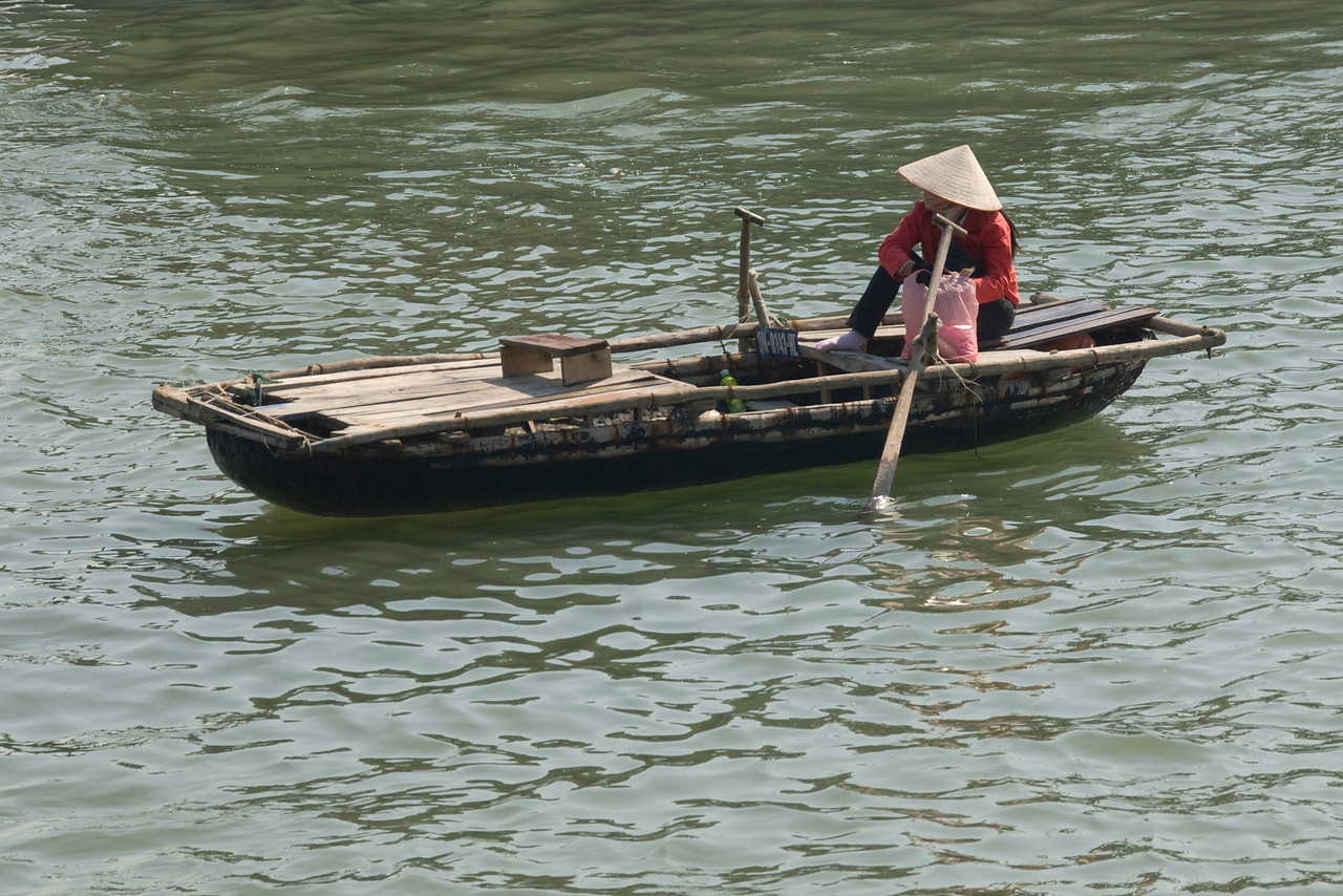 Woman sits on a row boat in Ha Long Bay, Vietnam