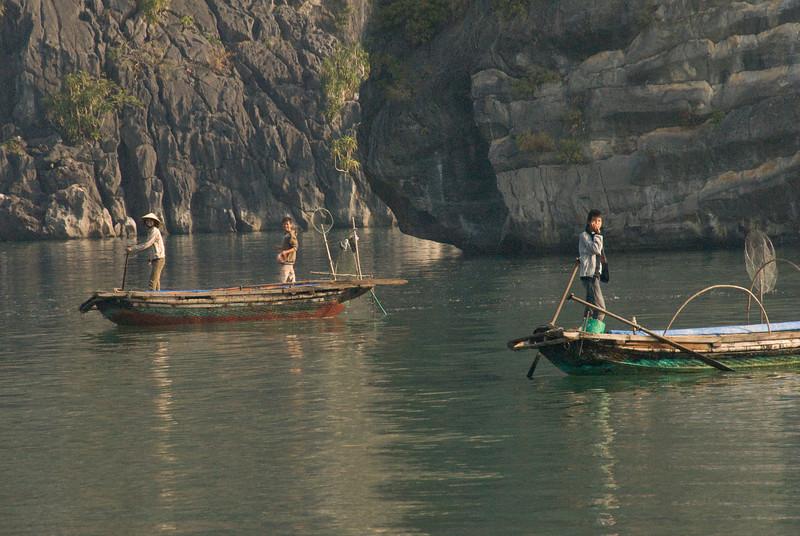 Fishermen on boats in Ha Long Bay, Vietnam