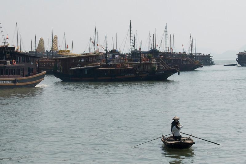 Women in a row boat near large ships - Ha Long Bay, Vietnam
