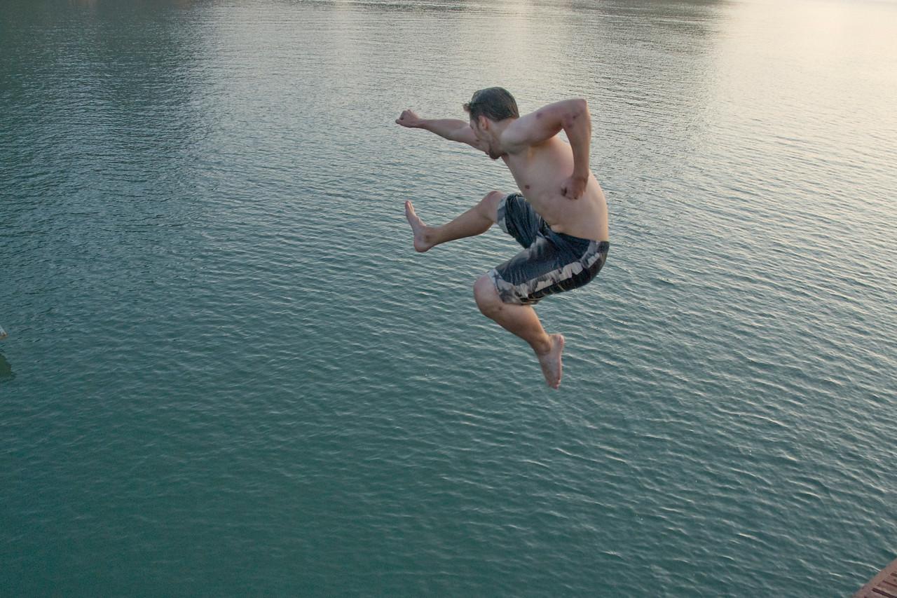 Man playfully diving off the boat - Ha Long Bay, Vietnam