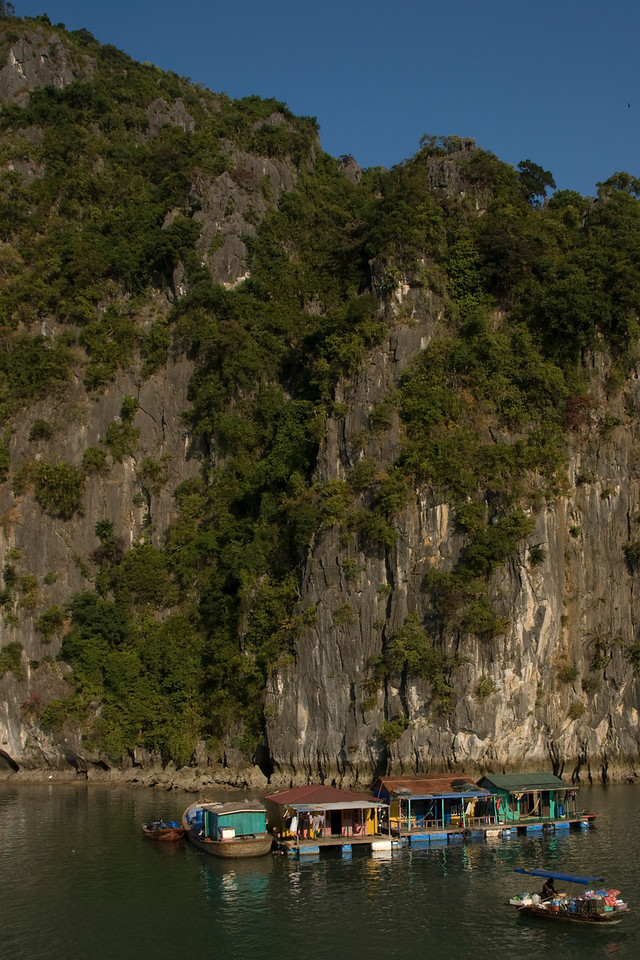 Wooden floating houses against steep cliffs in Ha Long Bay, Vietnam