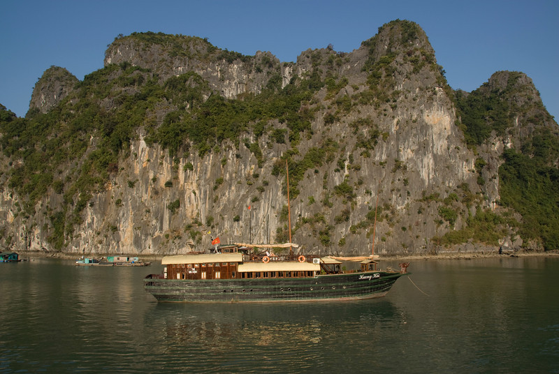 Tourist boat passing by cliffs in Ha Long Bay, Vietnam