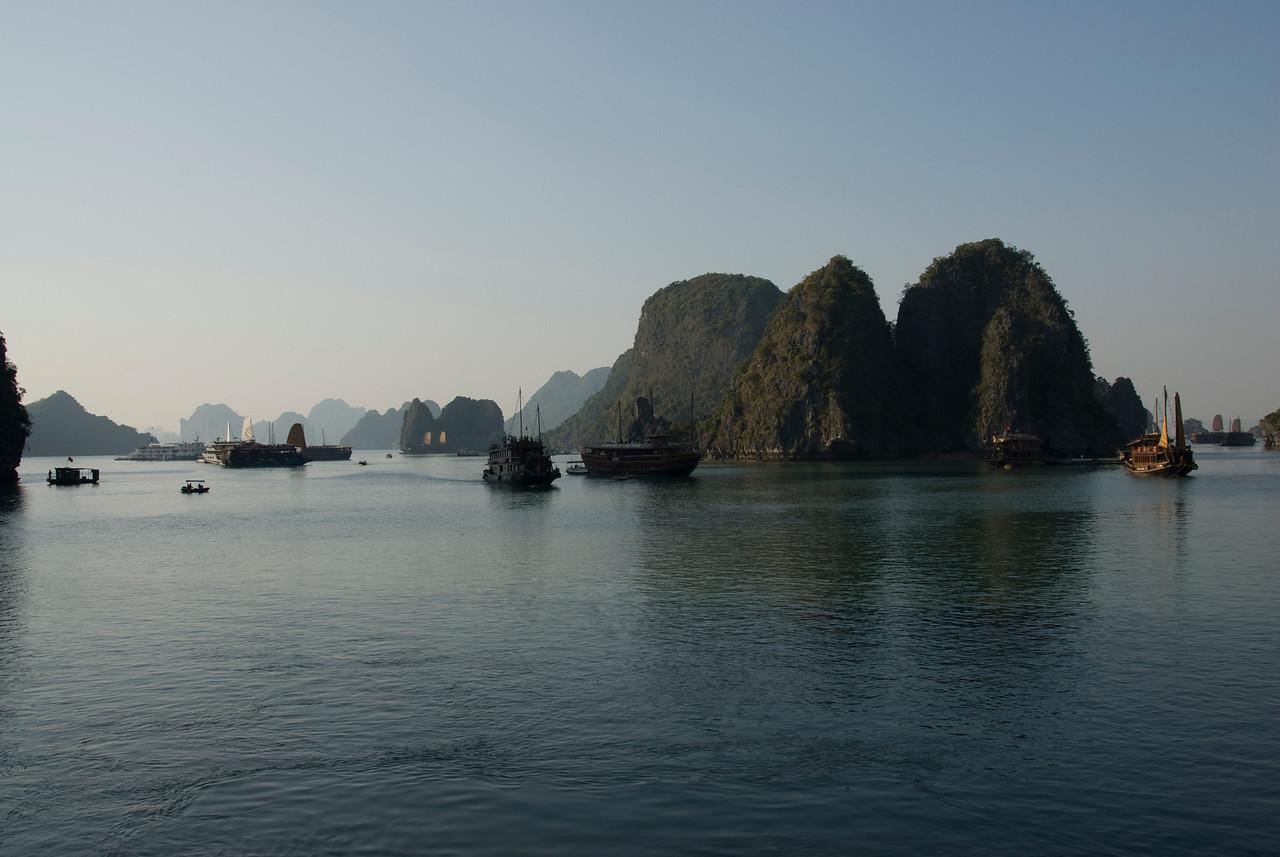 Boats cruising the water next to islands in Ha Long Bay, Vietnam