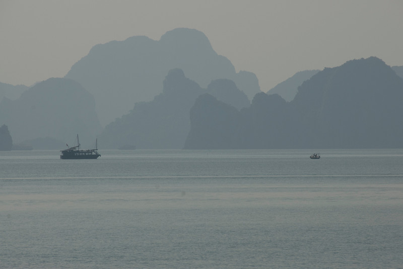 Boats cruising the bay against a silhouette of islands - Ha Long Bay, Vietnam