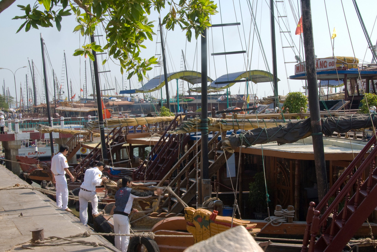 Men working on ships at dock - Ha Long Bay, Vietnam